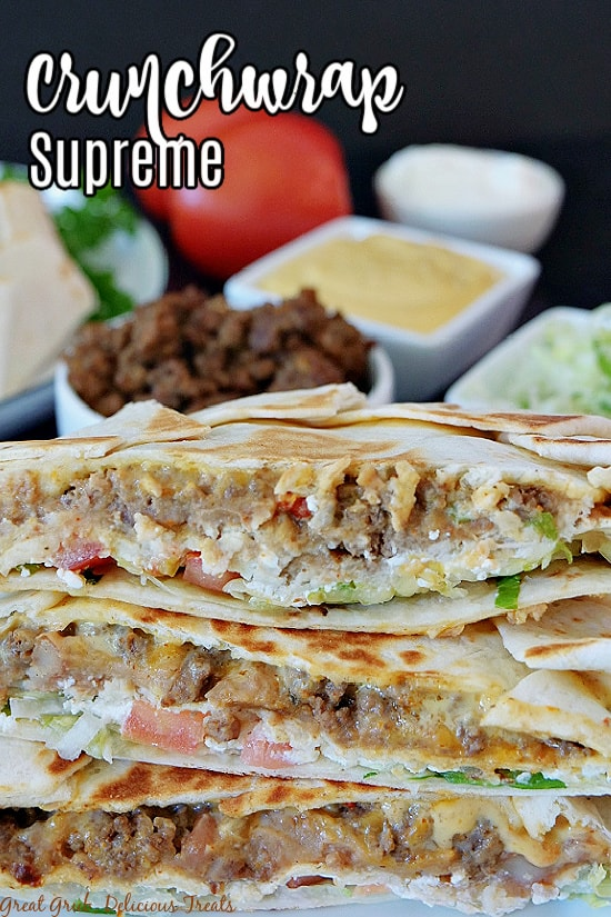 Crunchwrap Supremes cut in half and stacked on top of each other with a bowl of meat, a bowl of nacho cheese, a bowl of sour cream, a bowl of shredded lettuce, and a tomato in the background with the title in the top left corner.