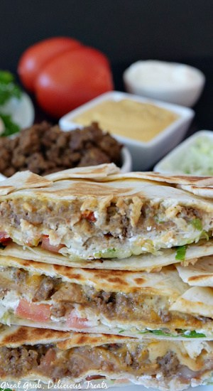 A close up picture of Crunchwrap Supremes with taco meat, nacho cheese, sour cream, shredded lettuce, and tomatoes in the background.