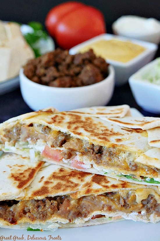 A close up picture of a Crunchwrap Supreme cut in half and stacked on top of each other with taco meat, nacho cheese, shredded lettuce, sour cream, and tomatoes in the background.