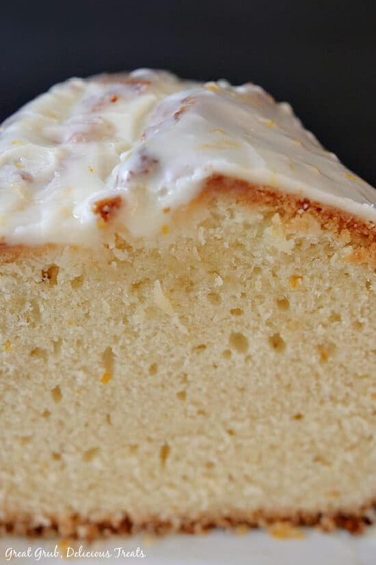 A close up view of orange pound cake loaf showing the cake and the orange glaze.