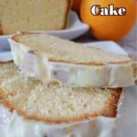 A white plate with 2 slices of pound cake on it, with half a loaf of orange pound cake and 2 oranges in the background.