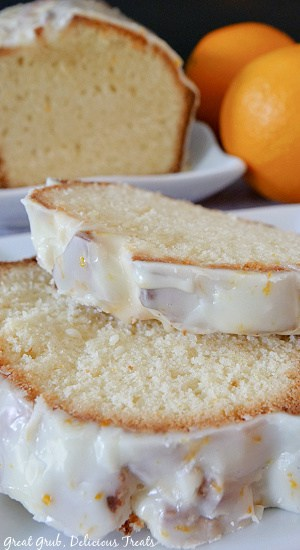 A white plate with 3 slices of orange pound cake on it, with 2 oranges in the background.