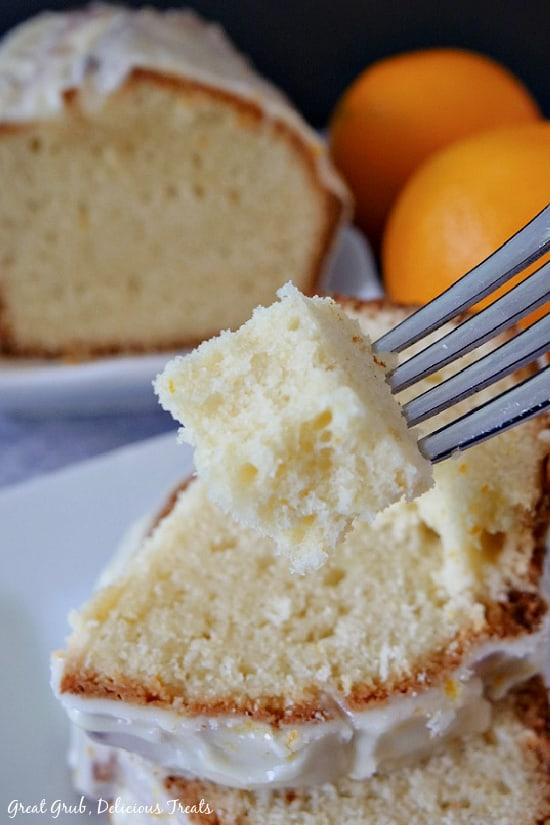 A bite of pound cake on a fork with a loaf of pound cake in the background.