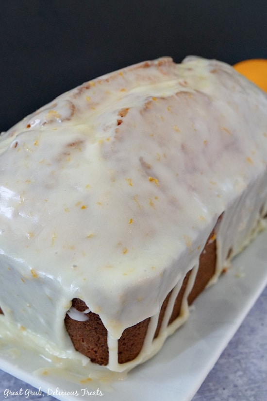A pound cake loaf sitting on a white plate with a white glaze on top of it, covering the entire loaf.