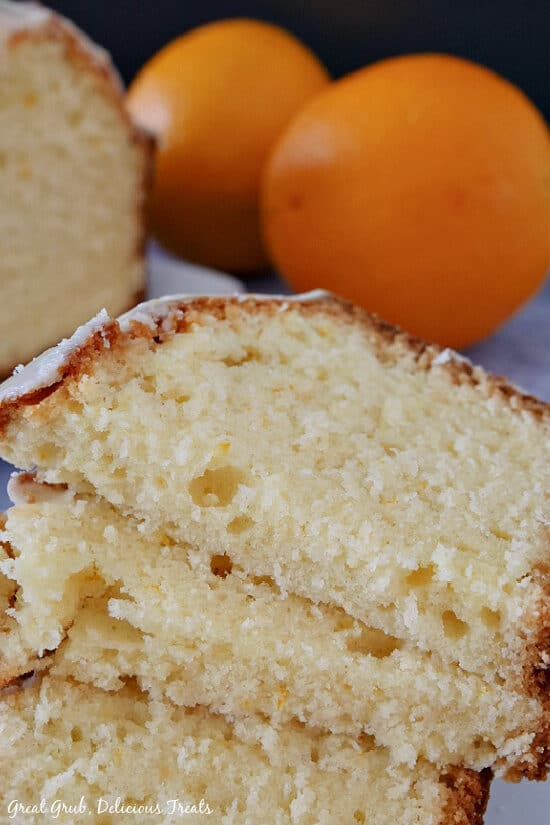 Three slices of orange pound cake stacked on top of each other with the loaf and two oranges in the background.