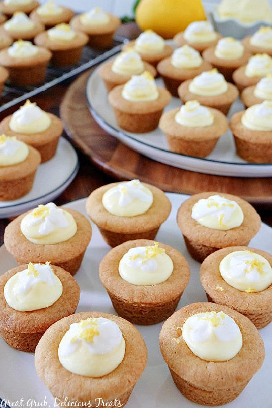 A few white plates filled with mini lemonade pie cookie cups.