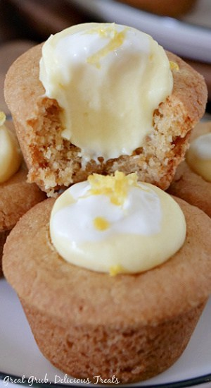 A close up of two mini lemonade pie cookie bites with a bite out of one of them.