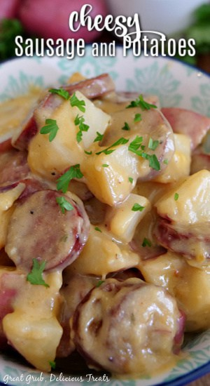 A white and green bowl filled with sausage and potatoes with a delicious cheese sauce.