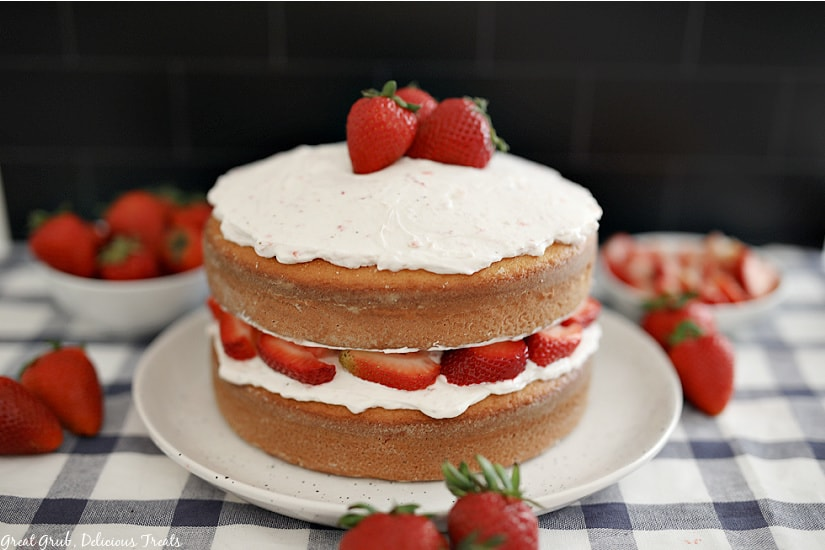 A whole strawberry shortcake cake on a white plate with fresh strawberries placed around on a blue and white checkered placemat.
