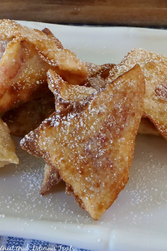 Raspberry Cream Cheese Wontons stacked on a white plate and dusted with powdered sugar.