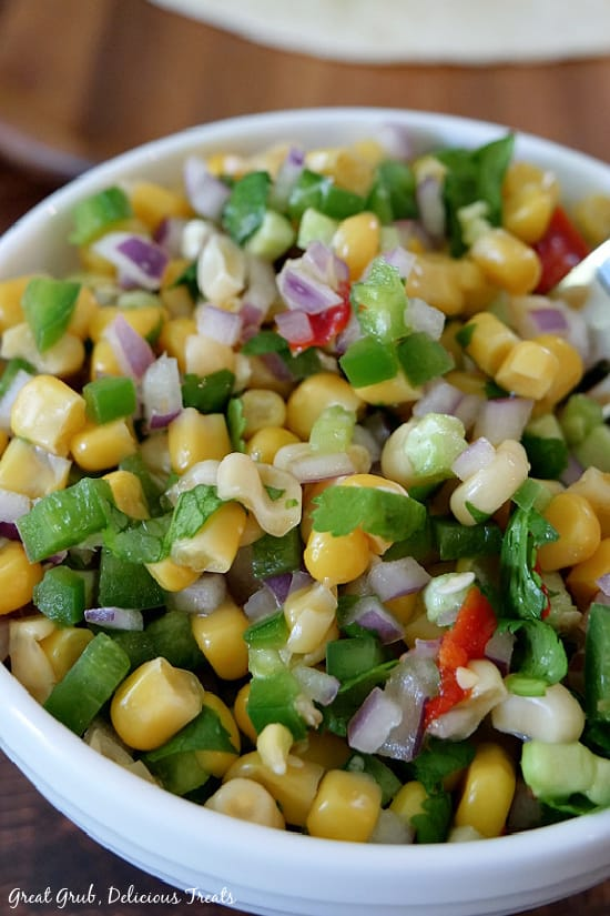 A white bowl filled with Southwest Corn Salsa which is corn, diced jalapenos, red onions and cilantro.
