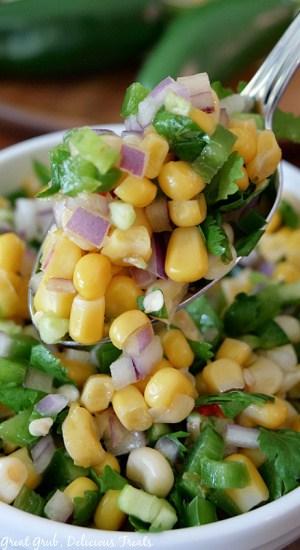 A close up shot of a spoonful of southwest corn salsa.