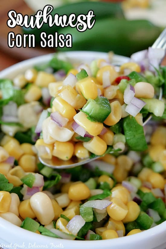 A close up photo of a white bowl filled with Southwest Corn Salsa with a big spoonful held up over the bowl.