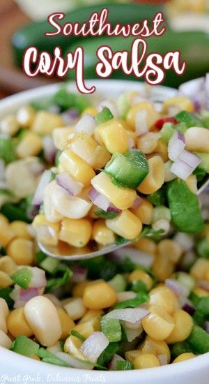 A super close up photo of a spoonful of Southwest Corn Salsa held up over a white bowl filled with a serving of the salsa.