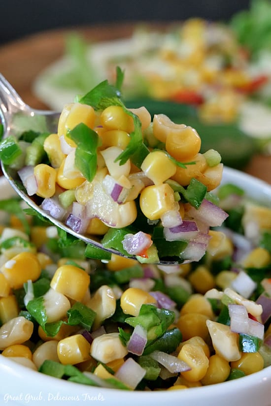 A white bowl filled with a serving of Southwest Corn Salsa and a spoonful held up a little above the bowl.