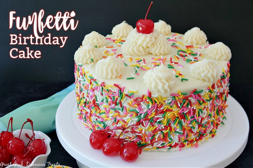 A funfetti cake with buttercream frosting and candied sprinkles all over the sides of the cake with a cherry on top sitting on a white cake plate.