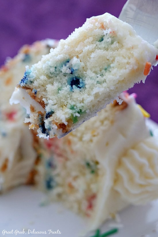 A close up photo of a bite of funfetti cake on a fork held above a slice of cake that is one a white plate.