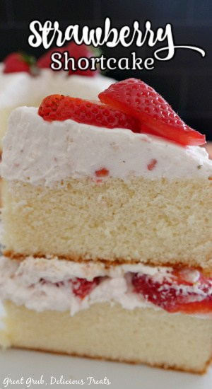 A close up photo of a piece of strawberry shortcake cake showing the two cake layers, the homemade whipped cream and fresh strawberries.