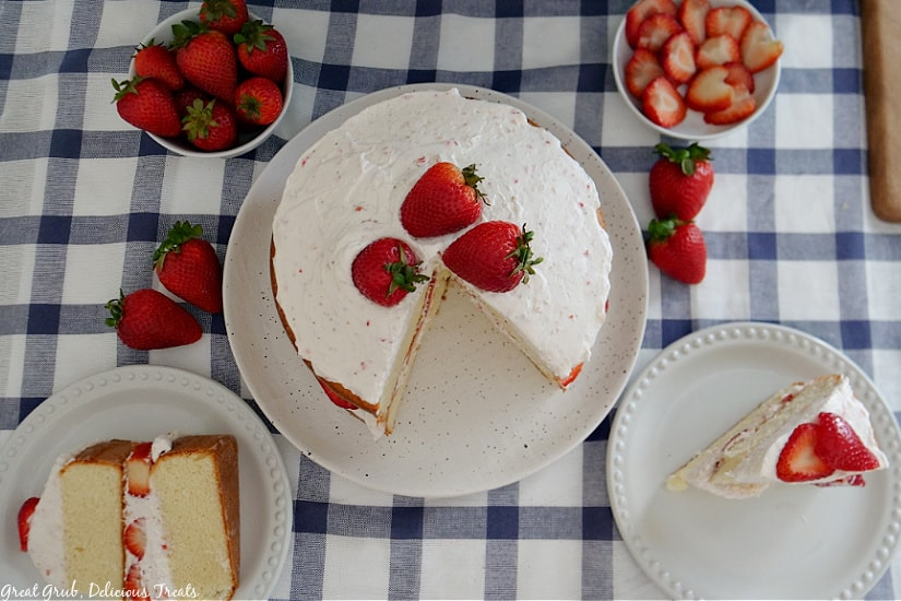 An overhead shot of a strawberry shortcake cake with two slices of cake on white plates.
