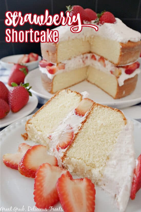 A slice of strawberry shortcake on a white plate with sliced strawberries on the plate too, and the whole cake in the background.
