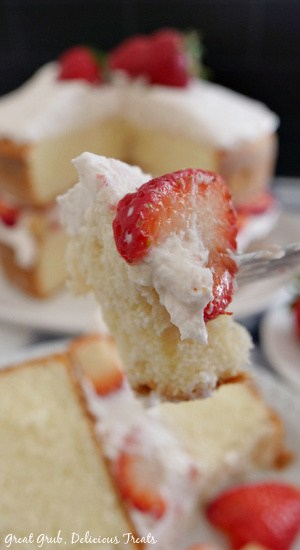 A photo of a fork with a bite of strawberry shortcake cake on it with the cake in the background.
