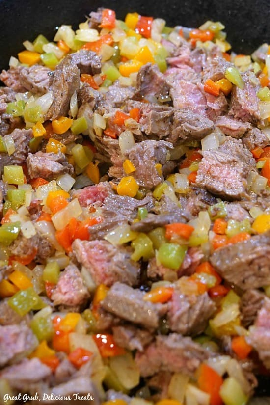 Beef flank steak with three different bell peppers and onions, seasoned deliciously and cooked until tender in a pan.