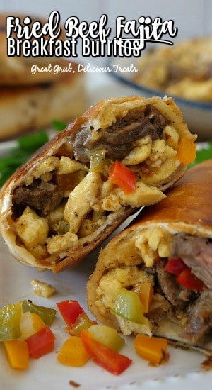 A close up photo of a beef fajita breakfast burrito, cut in half showing the ingredients, on a white plate.