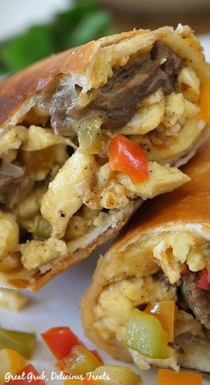 A super close up photo of a beef fajita breakfast burrito cut in half with the eggs, beef, pepper and onions showing stuffed into the tortilla.