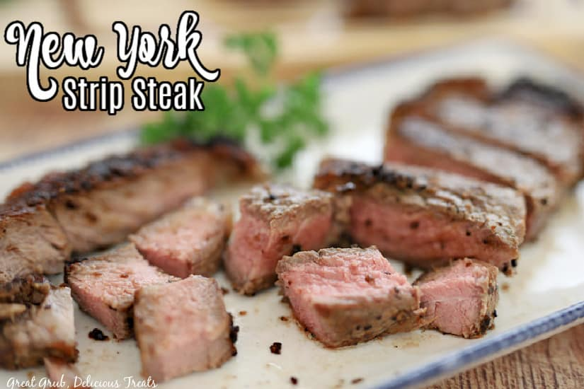 A white plate with blue trim that has a New York strip steak on it that has been cut into bite size pieces.