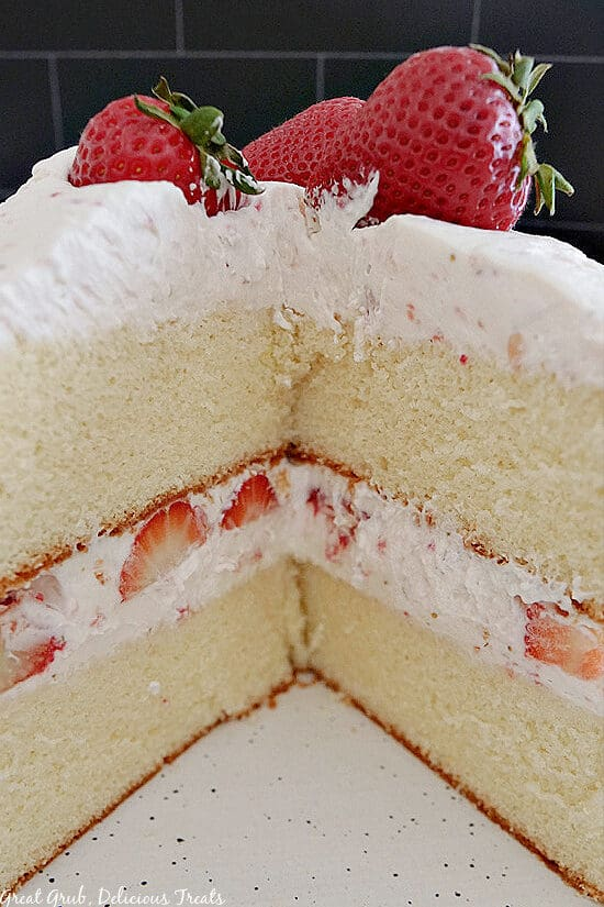 A close up shot of a two layered strawberry shortcake cake with homemade whipped cream and fresh strawberries.