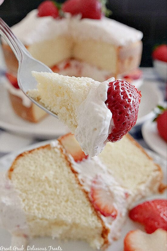 A bite of strawberry shortcake cake on a fork held up close to the camera with the cake underneath and in the background.