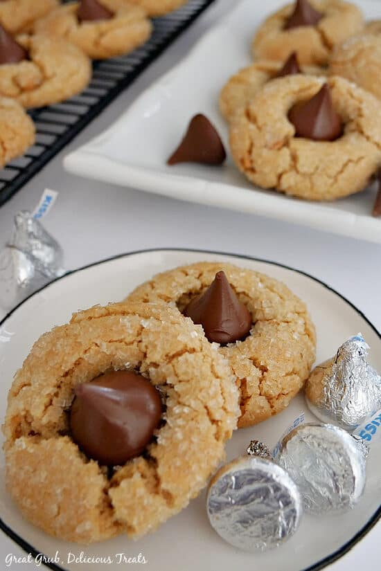 A white plate with two peanut butter blossom cookies on it along with 3 chocolate kisses, and more cookies in the background.