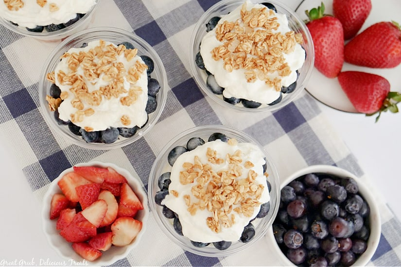 An overhead photo of strawberry blueberry parfaits on a white and blue checkered towel, will bowls of fresh strawberries and blueberries.