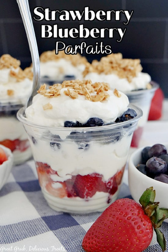 A clear plastic cup filled with whipped cream, strawberries, blueberries, and granola.