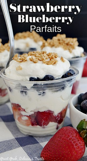A plastic cup with layers of whipped cream, strawberries, blueberries, and topped with granola.