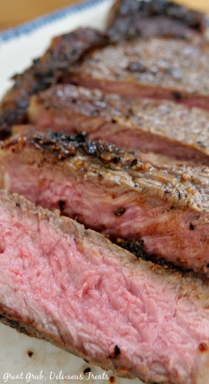 A super close up photo of a New York Strip Steak that has been cut into slices on a white plate with blue trim.