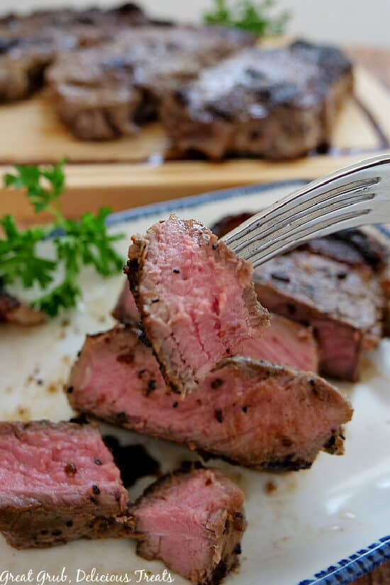 A close up photo of a bite of New York strip steak on a fork with additional bites of steak underneath on a white plate with blue trim.