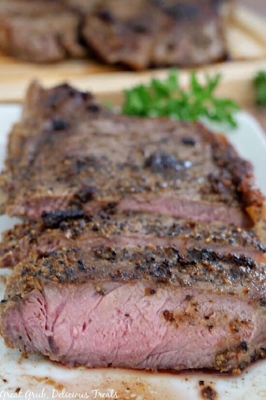 New York Strip Steak on a white plate showing the medium center of the steak.