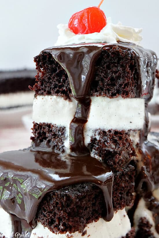 A white plate with two pieces of hot fudge cake stacked on top of one another, both with hot fudge dripping down the sides, topped with whipped cream and a cherry on top.
