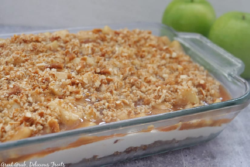 A 9 x 13 baking dish with apple cinnamon pretzel salad in it with two green apples in the background.