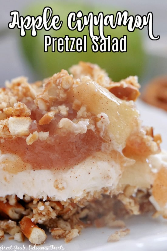 A white plate with a piece of apple salad, with crushed pretzel crust, a whipped cream filling, all topped with a cinnamon apple topping.