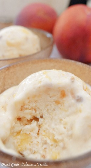 A scoop of peach cobbler frozen dessert in a gold bowl with peaches in the background.