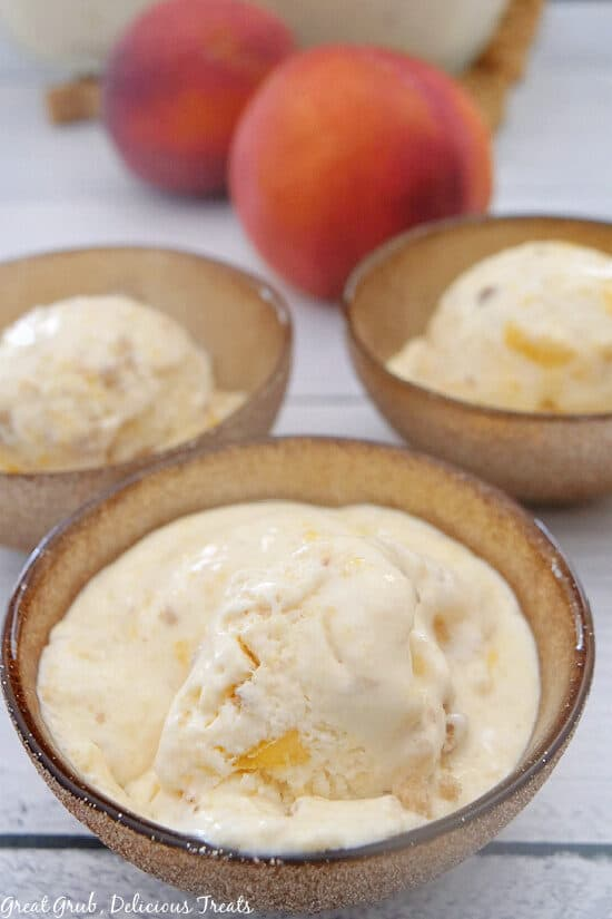 A close up of Peach Cobbler Frozen Dessert in a gold bowl with two other gold bowls filled with the frozen dessert and two whole peaches in the background.