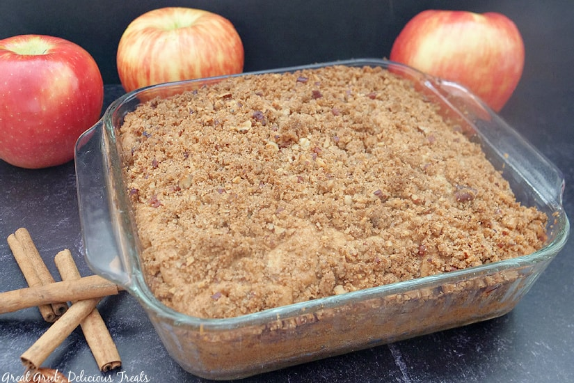 A horizontal picture of Apple Pecan Coffee Cake in a clear dish with whole apples and cinnamon sticks in the background.