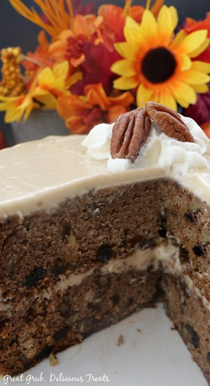A close up photo of an inside view of the apple spice cake showing the two layer with the frosting layer showing.