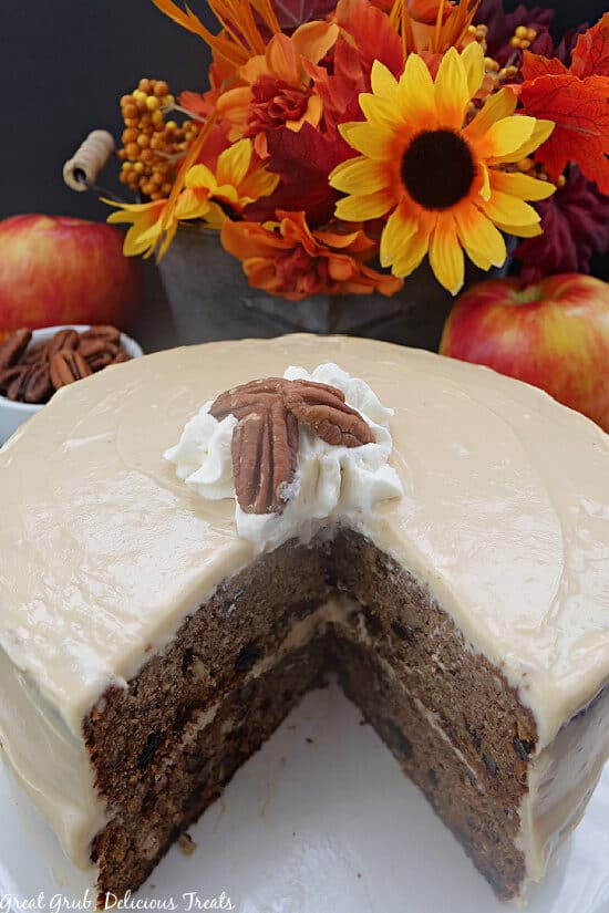 An apple spice cake with two slices removed on a white plate with fall foliage in the background.