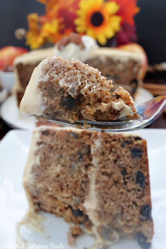 A fork with a bite of apple spice cake with the slice on a white plate.