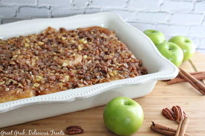A white 13 by 9 inch baking dish filled with caramel apple pecan sticky buns with 4 green apples, pecans and cinnamon sticks placed around the dish.