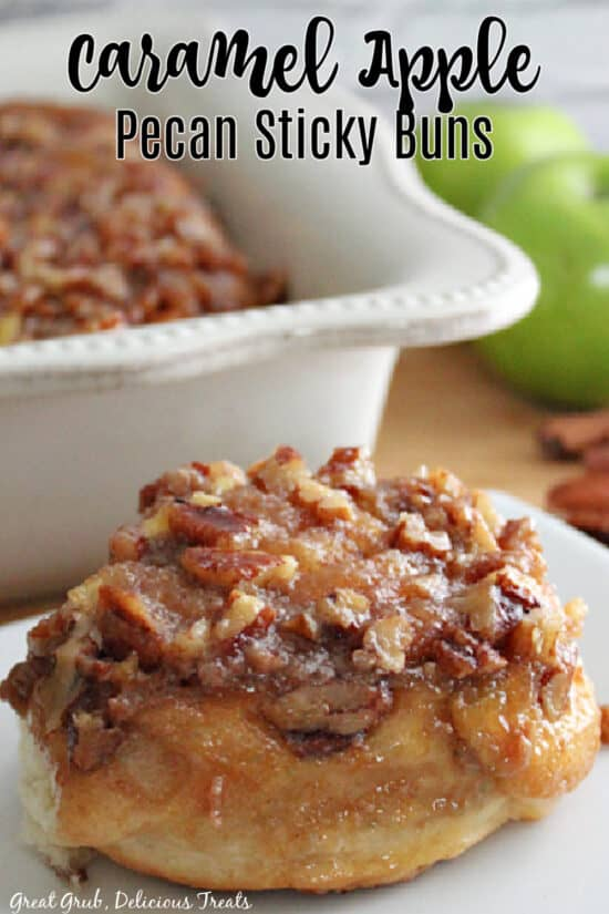 A white plate with a sticky bun placed on it and a baking dish in the background with more caramel apple pecan sticky buns in it.