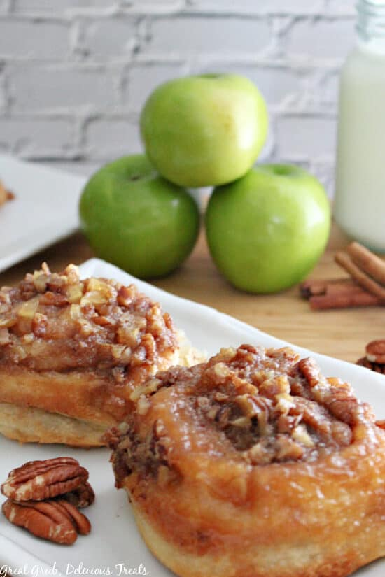 A white plate with two sticky buns on it with 3 green apples in the background.